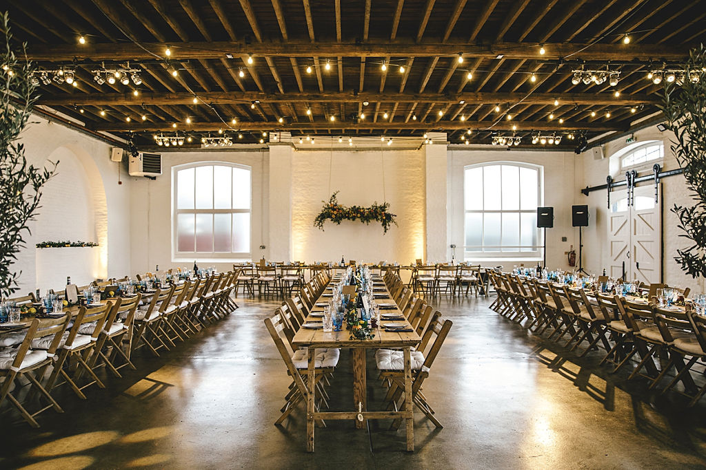 A contemporary and cool wedding at Trinity Buoy Wharf trestle table set up with festoon lights